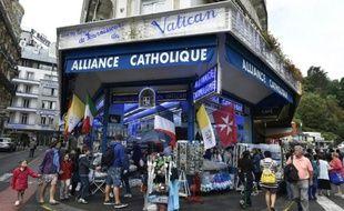 Des personnes se promènent devant des marchands de souvenirs à Lourdes en France, le 15 août 2015