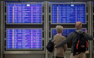 Des voyageurs contrôlent les écrans d'informations sur les vols à l'aéroport de Francfort, en Allemagne, le 9 novembre 2015
