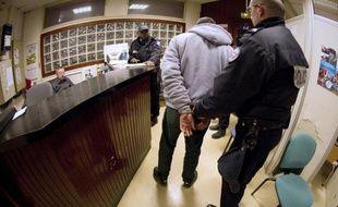 Un suspect amené menotté dans un commissariat le 9 février 2012 à Paris