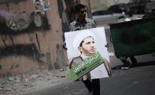 Un militant bahreïni tient une affiche à l'effigie du chef de l'opposition chiite cheikh Ali Salmane lors d'une manifestation pour protester contre son arrestation, le 12 juin 2015 à Diraz, à l'ouest de Manama