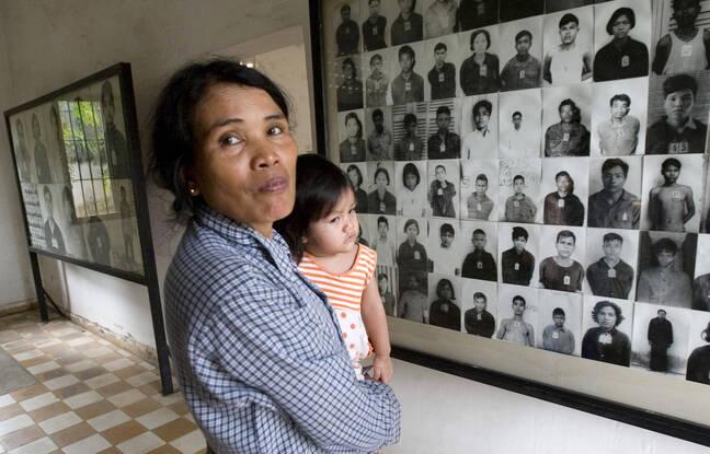 Une cambodgienne et son enfant en 2009 devant des photos de victimes de Douch sur le site de la prison S-21 à Phnom Penh.