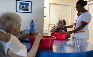 Une aide-soignante s'occupe de dames âgées dans un Ehpad près de Lyon.