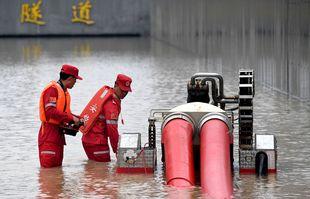 Des pompiers pompant l'eau de pluie d'un tunnel routier à Zhengzhou, capitale de la province du Henan (centre de la Chine), le 22 juillet 2021.