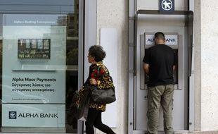 Un Grec en train de tirer de l'argent à un distributeur alors que la question de la sortie de la Grèce de la zone euro se pose.