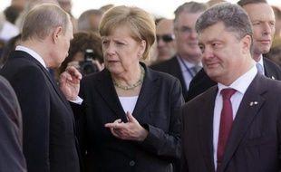 La chancelière allemande Angela Merkel s'entretient avec le président russe Vladimir Poutine (g) et le président élu ukrainien Petro Poroshenko (d) à Ouistreham en Normandie lors des commémorations du 70e anniversaire du Jour J, le 6 juin 2014
