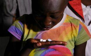 Une jeune kenyane de 13 ans Claudia Aulo prend ses médicaments pour traiter le sida le 9 novembre 2015 dans le comté de Homa Bay (ouest du Kenya)