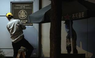 Un ouvrier détache la plaque du consulat américain de Chengdu, le 26 juillet 2020.
