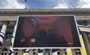 Un écran géant devant la Bourse de Paris diffuse en direct la finalisation de l'album de Kanye West.