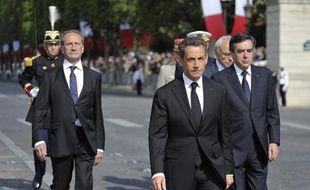 Le président de la République, Nicolas Sarkozy, entouré du ministre de la Défense, Gérard Longuet (à gauche) et du Premier ministre, François Fillon (à droite), lors du défilé du 14-Juillet, à Paris, le 14 juillet 2011.