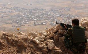 Un combattant kurde surveille les alentours depuis le sommet du mont Zardak, à environ 25 kilomètres à l'est de Mossoul, le 6 août 2015