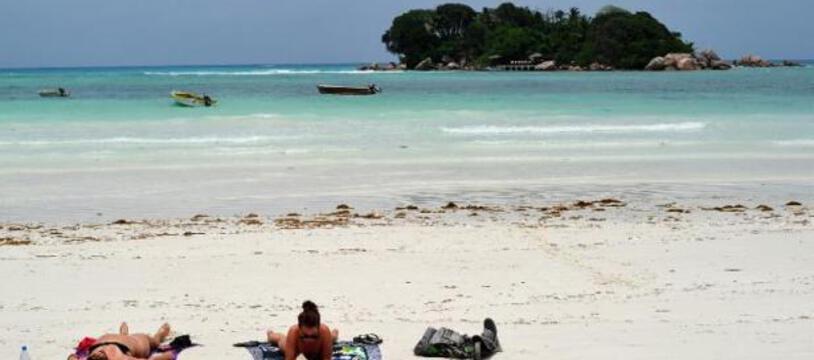 Des touristes bronzent sur une plage de l'île de Praslin aux Seychelles le 6 mars 2012