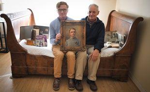 Patrice Retour et son cousin Hervé Graffe posent avec une peinture de leur grand-père Maurice retour mort en 1915 durant la Première Guerre mondiale.