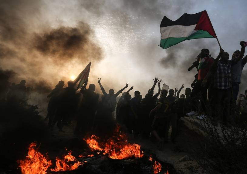 Palestinian protesters wave national flags as they stand near burning tyres during a demonstration on the beach near the maritime border with Israel, in the northern Gaza Strip, on October 22, 2018.