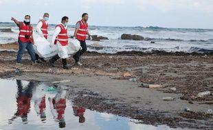 Des membres de la Croix-Rouge portent le corps d'un migrant à Khoms (Libye), le 25 octobre 2015.