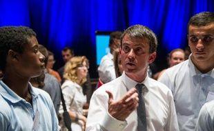 Le Premier ministre Manuel Valls (c) rencontre des jeunes lors après un comité interministériel sur la jeunesse, le 3 juillet 2015 à Besançon