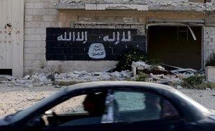 Une voiture passe devant les ruines d'une usine, dont le mur a été peint aux couleurs d'un groupe djihadiste, le 18 novembre 2014, à Alep en Syrie