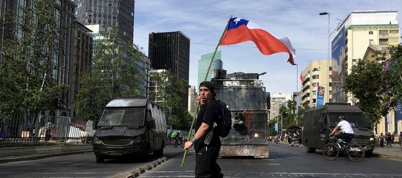 Un manifestant face aux forces de l'ordre à Santiago du Chili, le 26 octobre 2019.