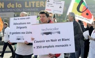 """Employees of the Technicolor company demonstrate with a placard reading """"The future in black and white, 350 jobs threatened !"""" on March 13, 2012 in front of their plant in the western city of Angers, to protest againt the foreseen closure of the company. Three hundred and 50 jobs would be cut in the case of closure. AFP PHOTO FRANK PERRY"""