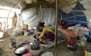 Une famille de survivants vit toujours dans une tente le 21 avril 2016 près de l'aéroport de Katmandou, un an après le tremblement de terre qui a frappé le Népal