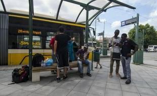 Un groupe de migrants attend un tram dans la ville hongroise de Szeged le 3 août 2015 après avoir franchi la frontière entre la Serbie et la Hongrie