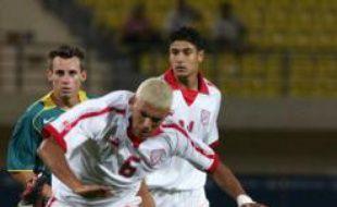 Le milieu de terrain de la Tunisie, Hocine Ragued (en blanc) lors d'un match des JO d'Athènes en 2004 face à l'Australie.