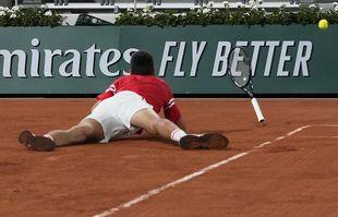 Le Serbe Novak Djokovic tombe alors qu'il affronte l'Italien Matteo Berrettini en quart de finale des Internationaux de France de tennis au stade Roland Garros le mercredi 9 juin 2021 à Paris.