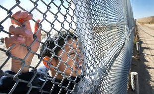 Un enfant regarde à travers le grillage de la frontière entre le Mexique et les Etats-Unis, le 24 décembre 2013.