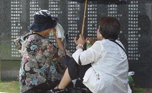 Des Japonaises se recueillent au pied d'un monument de marbre noir où sont inscrits les noms des défunts, le 23 juin 2015 à Okinawa