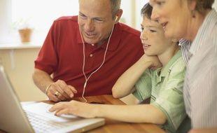 Des grands-parents jouent avec leur petit-fils sur le web.
