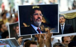 Des gens tiennent une photo du président égyptien Mohamed Morsi lors d'une cérémonie commémorative de funérailles symbolique le 18 juin 2019 à la mosquée Fatih à Istanbul.