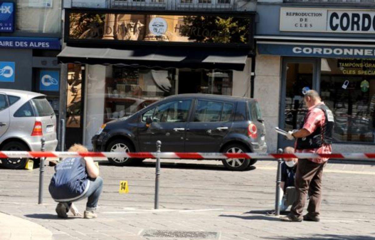 Des policiers sur les lieux du braquage survenu à Grenoble, le 10 août 2012. – AFP PHOTO /JEAN-PIERRE CLATOT