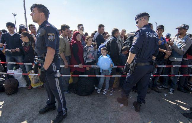 Des agents de police devant des migrants attendant de pouvoir embarquer dans des bus, du côté autrichien de la frontière austro-hongroise, le 12 septembre 2015, près de Nickelsdorf.