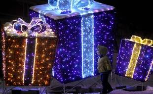 A child walk past a Christmas decoration resembling gifts on the Zamkowy Square in Warsaw, Poland, Sunday, Dec 23, 2012, one day ahead of Christmas Eve. (AP Photo/Alik Keplicz)/XAK151/709004918200/1212232016