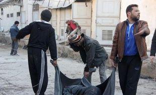 Des rebelles transportent le corps d'une victime à Alep, le 8 janvier 2014
