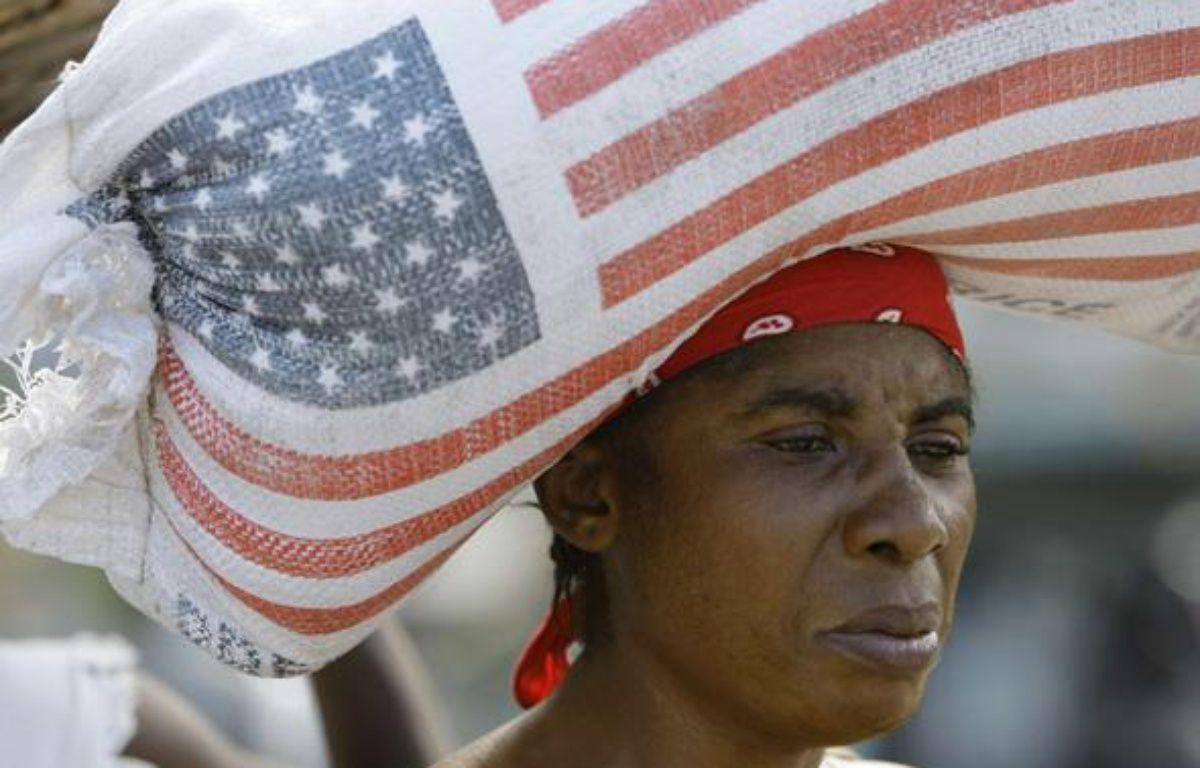Une femme porte un sac de riz donné par l'Usaid, en Haiti, le 16 janvier 2010. – Lynne Sladky/AP/SIPA