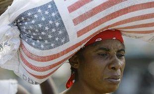 Une femme porte un sac de riz donné par l'Usaid, en Haiti, le 16 janvier 2010.