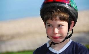 Photo d'illustration: Un jeune garçon porte un casque de vélo.