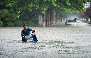 Un homme roule sur une route gorgée d'eau à Zhengzhou, capitale de la province du Henan (centre de la Chine), le 20 juillet 2021.