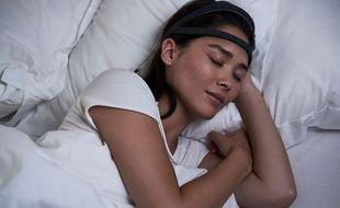 Une femme dort avec le bandeau Dreem, illustration.