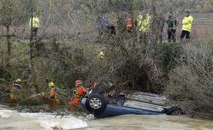 Des sauveteurs près d'une voiture dans laquelle ont péri une mère et ses deux enfants près de Cruviers-Lascours, le 15 novembre 2014