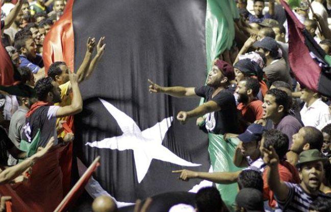 Des insurgés libyens envahissent le QG de Mouammar Kadhafi, le 23 août 2011, à Tripoli.