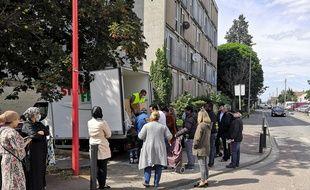 Les gens attendent de recevoir leur colis des Restos du cœur, à Bobigny, le 13 mai 2020.