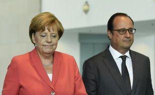 La chancelière allemande Angela Merkel (G) et le président français François Hollande (D) lors d'une conférence de presse commune à la chancellerie, le 24 août 2015 à Berlin