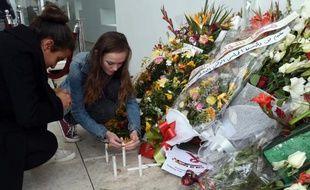 Des touristes allument des bougies le 27 mars 2015 devant le Musée national du Bardo à Tunis à la mémoire des 21 personnes tuées dans l'attaque jihadiste du 18 mars