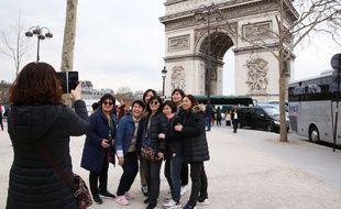 Un groupe de touristes chinois devant l'Arc de Triomphe à Paris.