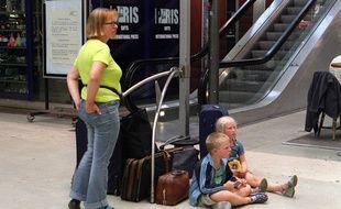 Une famille attend son train pour partir en vacances