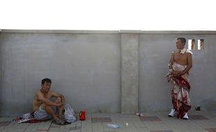 Des hommes patientent en attendant d'être pris en charge par les secours, après les explosions à Tianjin, en Chine, dans la nuit du 12 au 13 août.