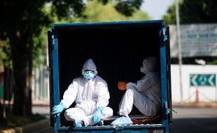 Des hommes vêtus d'équipements protecteurs à New Delhi, le 4 mai 2020.