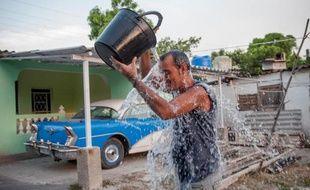 Un cubain se rafraîchit avec un seau d'eau dans une rue de La Havane, le 27 août 2014 alors que le pays est frappé par la canicule