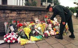 Un officier de la Royal Ulster Constabulary dépose des fleurs devant le site d'un attentat à Omagh le 17 août 1998